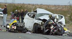 Rescuers and victims are seen at the site of a collision involving a car and several motorcycles on a remote desert highway near Ocotillo, Calif., Saturday.