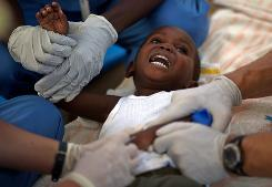 A child with cholera symptoms is treated Monday at a hospital in Archaie, Haiti. The Pan American Health Organization estimates cholera will sicken at least 200,000 people.