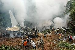 Crews work amid the smoldering wreckage of an Air India Boeing 737-800 that crashed on landing in Mangalore, India.