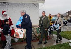"Retired sheriff's deputy Sandy Hale portrays Santa as he and other county public safety officers bring gifts to Ruben Hernandez, 9, left as part of the Debbie Chisholm Memorial Foundation's ""Spirit of Christmas"" program."