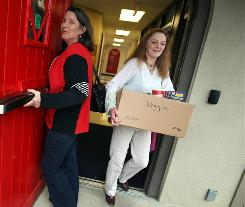 Marilyn Mussar holds the door for Marlene Thornton as she carries a box of food from St. Luke's Community House to her car to feed her family on Jan. 22.