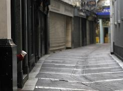 A man takes shelter in a doorway, left, as he begs for money on a deserted street in central Dublin, on Friday.