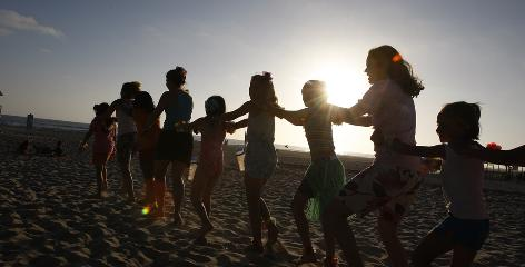 Children at Operation Purple Camp dance on the beach during an outing to Del Mar Beach at Camp Pendleton. The children of servicemembers wounded in war gather together in a camp designed and established by the National Military Family Association. 