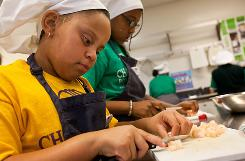 Codi Aldana, 8, left, and Alyssa Johnson, 11, cut shrimp for dumplings during the Common Threads cooking class on Nov. 3 in Los Angeles.