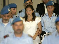 In this 2008 file photo, Amanda Knox, center, is escorted by Italian penitentiary officers from Perugia's court after a hearing. The American student's appeals trial opens Wednesday.