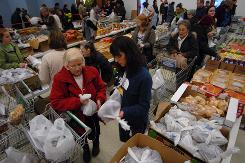 Joan Notti, left, receives assistance from volunteer Shannon O'Connell as they gathered enough food at St. Patrick's Church to make a Thanksgiving meal during the Food Bank of Alaska Thanksgiving Blessing. The event is a citywide distribution of food for those less fortunate.