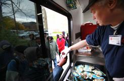Lloyd Johnson, 42, a driver for the Bed & Bread Club, hands food to clients from his truck in October. With increased demands for services, the Salvation Army's the Harbor Light System and Acres of Hope Detroit need a strong turnout in their annual holiday fundraising campaign.