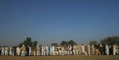 Pakistan flood survivors line up to receive relief goods from Al-Furqan Foundation in the outskirts of Peshwar on Nov. 8.