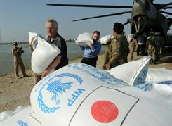 U.S. Ambassador to Pakistan Cameron Munter, left, unloads relief goods from a U.S. helicopter at the flooded area of Jacobabad on Oct. 30.