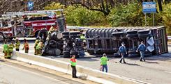 Police and firefighters work at the scene after a truck overturned near Wilmington, Del., on Wednesday.
