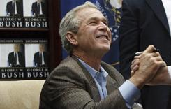 Former President George W. Bush  shakes hands with an man after autographing a copy of his memoir, Nov. 19, in Sandy, Utah.
