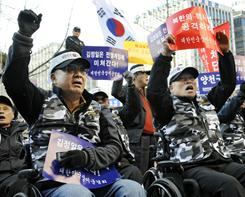 South Korean veterans in their wheelchairs raise their fists and shout anti-North Korean slogans during a rally in Seoul on Monday.