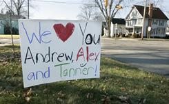 A sign in front of a home shows the names of three missing brothers, Sunday in Morenci, Mich.