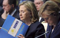 Secretary of State Hillary Rodham Clinton, center, reads a document as she sits next to German Chancellor Angela Merkel at the start of the OSCE Summit at the Palace of Independence in Astana, Kazakhstan on Wednesday.