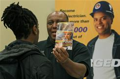 Lawrence Hyson talks to a job seeker about becoming an electrician during a job fair at Prince George's Community, on Nov. 4 in Largo, Md. The Federal Reserve recently forecast that the jobless rate will still be hovering around 9% at the end of 2011 and will fall slowly to about 8% by the end of 2012.