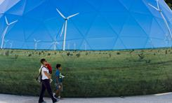 A family passes by one of the stands promoting green energy at the Climate Village in Cancun, Mexico, on Saturday in the framework of the COP16 summit.