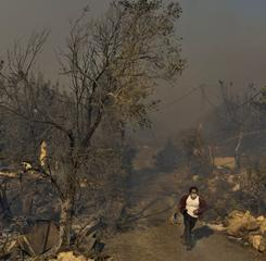A resident carrying a bucket runs through a burnt area in Ein Hod, northern Israel, Saturday,