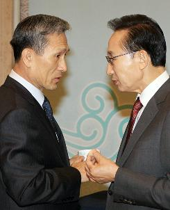 South Korean President Lee Myung-Bak, right, talks with Defense Minister Kim Kwan-Jin before a cabinet meeting in Seoul on Tuesday.