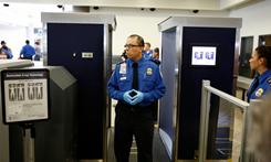 TSA agents stand near a full-body scanner at Los Angeles International Airport on Nov. 22. The Centers for Disease Control and Prevention recommends that the TSA takes steps to protect workers against excessive exposures to radiation.