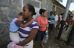 Venezuelans displaced by flooding line up for food and water outside a fire station on Monday. President Hugo Chavez said Sunday that he would force privately owned hotels to help shelter thousands of people who left their homes due to weeks of torrential rains.