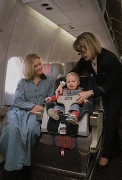 United Airlines flight attendant Jan Brown, right, demonstrates the use of a child safety seat on an airplane at Dulles International Airport in Chantilly, Va.