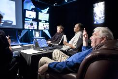 John Madden watches games with his development team at his Goal Line Productions facility in Pleasanton, Calif. Team members include Larry Richart, center, and Anthony White, right.