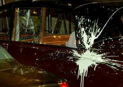 A broken window and splattered paint are seen on a car used to transport Britain's Prince Charles and Camilla the Duchess of Cornwall in London on Thursday, after it was attacked by protestors.