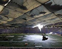 Snow falls onto the field through a hole in the collapsed roof of the Metrodome in Minneapolis on Sunday. The inflatable roof collapsed after a snow storm that dumped 17 inches on Minneapolis.
