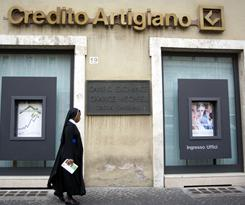 In this Sept. 21 file photo, a nun walks past a branch of Credito Artigiano's bank in Rome. Italian prosecutors contest claims by the Vatican bank that it is trying to comply with international rules to fight money laundering.