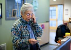 Willoughby Walshe, 73, talks on the phone at the Northgate Community Center in Seattle before teaching a piano lesson at the facility in November.