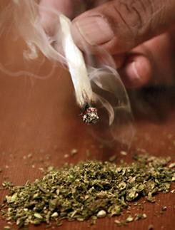 A marijuana user poses a joint over some ground marijuana last month in Tempe, Ariz.