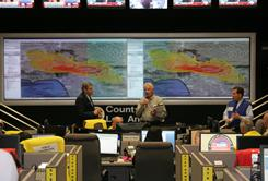 Computer-simulated fallout over Los Angeles is projected at Operation Golden Phoenix's command center, where county Health Director Jonathan Fielding, left, monitors possible effects.