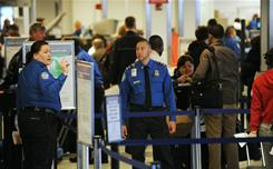 Two US Transportation Security Administration officers monitor passengers in a security line at La Guardia Airport in New York on Nov. 24.
