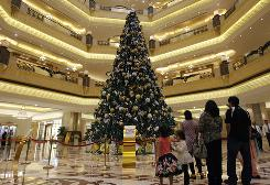 Tourists view a Christmas tree that has been adorned with $11 million worth of gold at the Emirates Palace hotel, in Abu Dhabi, United Arab Emirates, on Thursday.