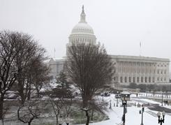 The Capitol is covered during the first snowfall of the season Thursday in Washington. House members debated a tax-cut measure.