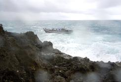 A boat approaches the rocky shore on Christmas Island just before it breaks up on the rocks last Wednesday, killing dozens.