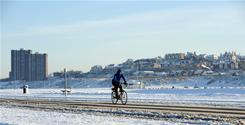 A man cycles along a snow covered road in New Brighton near Liverpool, England, on Sunday. London Heathrow, the world's busiest international passenger airport, remained paralyzed on Sunday due to snowfalls that wrecked Christmas commuter plans in Britain.