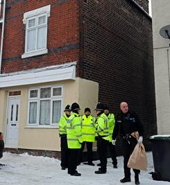 British policemen gather outside a property raided by police in Stoke-on-Trent, England, on Monday. British police arrested 12 men, ages 17 to 28, on suspicion of plotting an act of terrorism in a major operation involving pre-dawn raids across the country.