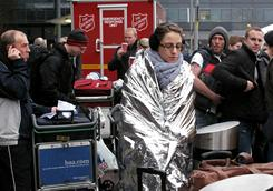A woman keeps warm in a foil blanket as she waits for flight information outside of Heathrow Airport's Terminal 3, west of London, on Tuesday. Thousands of travelers forced to sleep in airports and train stations faced more misery Tuesday as fresh snowfalls paralyzed transport systems.