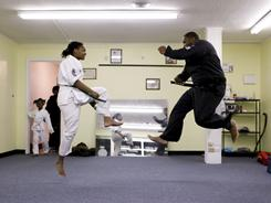 Anthony Smith instructs daughter Jamya Coleman, 12, in martial arts moves at Anthony's Martial Arts in Blytheville, Ark.