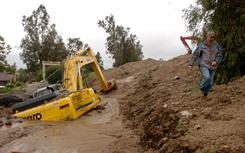 Steven Ball walks past buried heavy equipment after a mudslide flooded Bangor Avenue Wednesday in Highland, Calif.