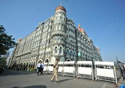 An Indian policeman patrols outside the Taj Mahal hotel in Mumbai on Friday. A manhunt was underway for four members of the same Islamist group that attacked the city in 2008.
