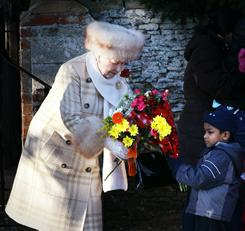 Queen Elizabeth II recieves flowers from a small boy after attending the Christmas Day Church Service at St. Mary's Church in Sandringham, England.