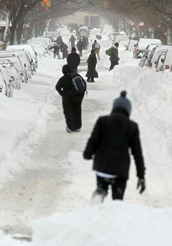 People walk through the snow Monday in Manhattan's East Village. A blizzard pounded the East Coast, delivering 20 inches of snow to New York City and snarling post-Christmas travel.