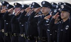 Officers salute as they watch the funeral of police Officer Ryan Bonaminio broadcast on a giant screen to an overflow crowd of mourners in Riverside, Calif., on Nov. 16. Bonaminio was shot and killed on Nov. 7 after he pulled over the driver of a stolen big-rig cab.