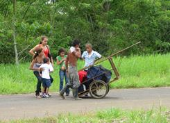 Migrants prepare to cross from Nicaragua into Costa Rica near Los Chiles last fall. Guides often use cars for luggage.
