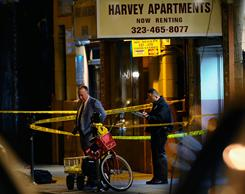 Los Angeles Police Department detectives stand outside the Harvey Apartments on Dec. 1. Fewer than 300 homicides are expected this year, Police Chief Charlie Beck said.