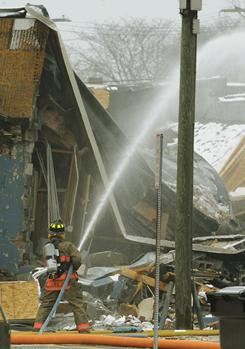 Firefighters respond after an explosion and collapse at the William C. Franks furniture store in Wayne, Mich., on Wednesday.