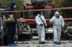 Police investigators collect evidence Thursday outside an Athens court building after a bomb exploded, causing widespread damage but no injuries.
