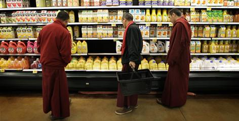 Tibetan monks, from left, Thabkhe Lo, Kunjo Baiji, and Lodoe Sangpo, look over the juice section at a supermarket in Atlanta.
